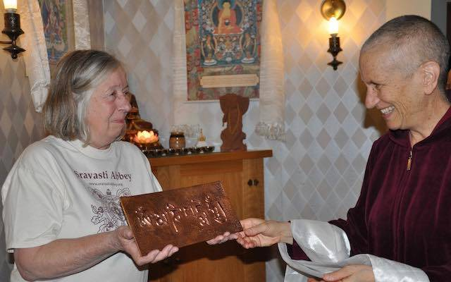 Woman hands embossed cover gift to nun