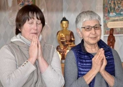 Tracy and Tanya chant the Buddha's mantra.