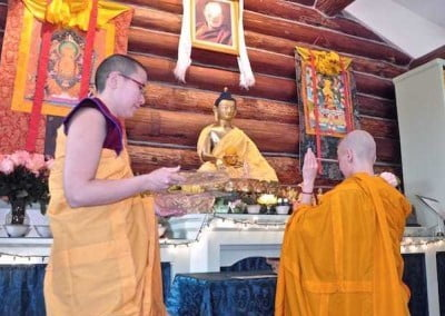 Vens. Jampa and Damcho offer a ceremonial stick to the Buddha, our fundamental teacher