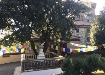 Prayer flags behind the main building wave their welcome as Ven. Chodron arrives at Istituto Lama Tsongkhapa.