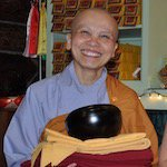 Nun wearing Vietnamese robes and bog smile has Tibetan robes in her hands.