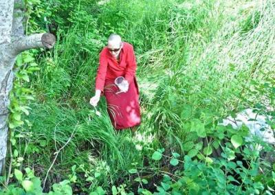 nun in tall grass near water