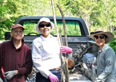 nun and laywoman pose near truck in forest