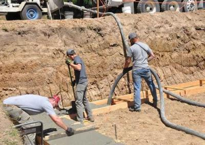 The crew works fast as concrete hardens quickly on a warm day.
