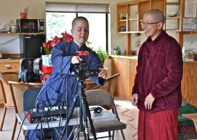 layperson with nun set up video camera