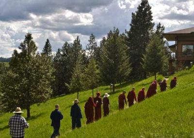 Line of monastics and laypeople walking by tall trees