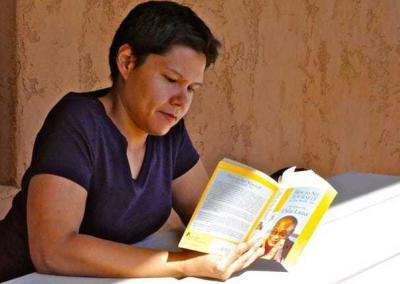 woman reading book outside
