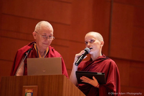 Two nuns at lectern with microphone at Sakyadhita conference.