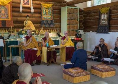 laywoman kneeling in front of seated nuns