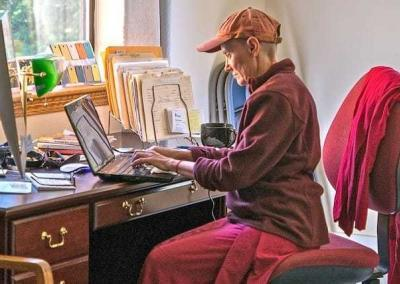 nun typing on a computer