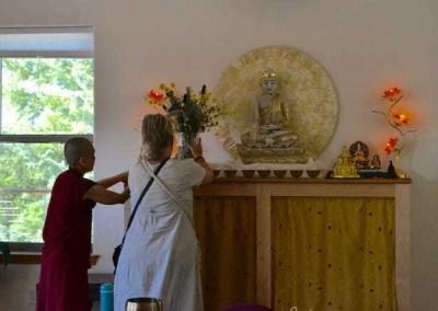 lay woman and nun put flowers on altar