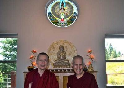 two nuns pose in front of Buddhist Statue