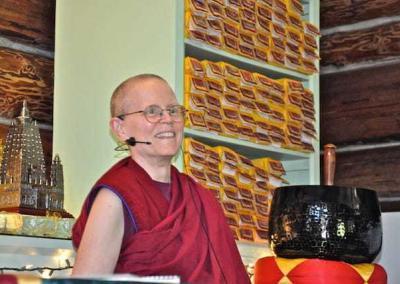 smiling nun in front of Tibetan texts