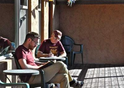two men reading on sunny deck