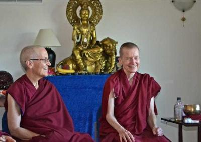two smiling nuns seated in front of Buddhist statue
