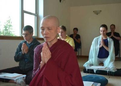 Nun praying in foreground of praying lay practitioner