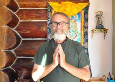 Smiling praying man standing in front of Buddhist image