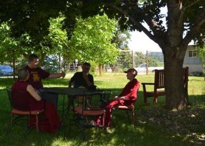 nuns and laypeople discussing at table under a tree