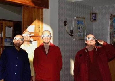 nuns and lay people wearing eclipse glasses