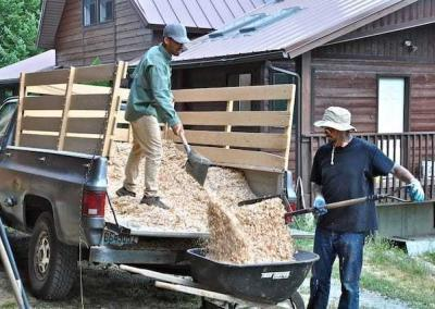 two lay men shoveling wood chips out of a truck bed