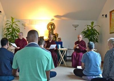 Group seated cross-legged before seated monastics