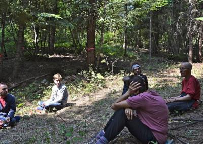 group sitting in forest talking