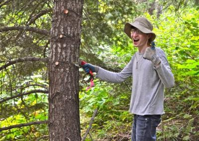 hatted man gives thumbs up in forest.