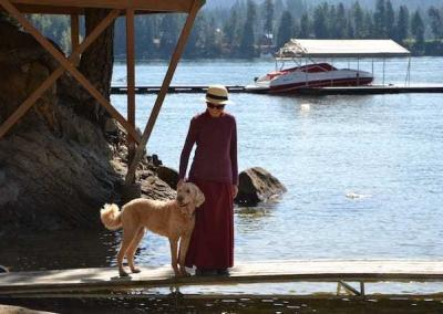 nun and dog on a dock by lake.