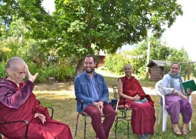 Monastics and lay people sitting on chairs in garden