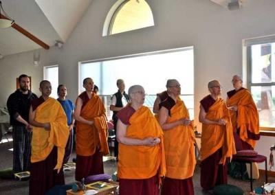 monastics and lay people standing facing to right
