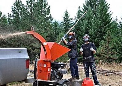 two people in safety gear running a wood chipper