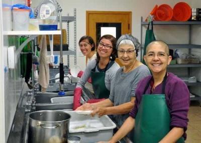 four women washing dishes