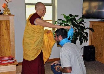 nun wraps blue scarf on kneeling layman