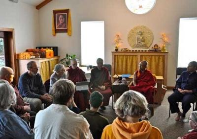 Monk speaking with group of lay people