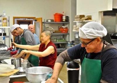 nun and lay men washing dishes