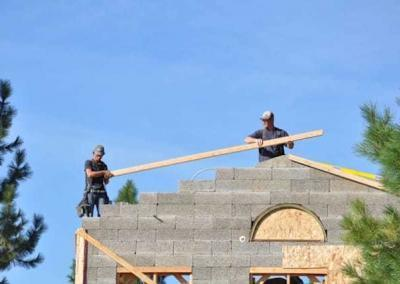 Two men placing wood on top of building wall
