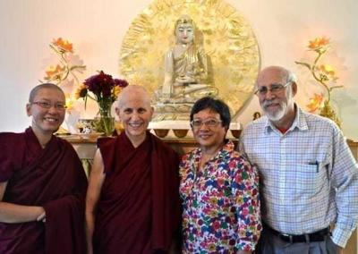 Lay man and woman pose with two nuns in front of Buddha statue