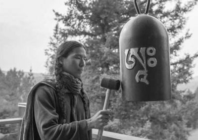 lay man striking Buddhist bell.