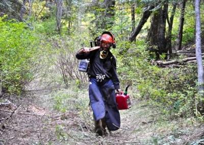 man dressed in protective clothing in forest.