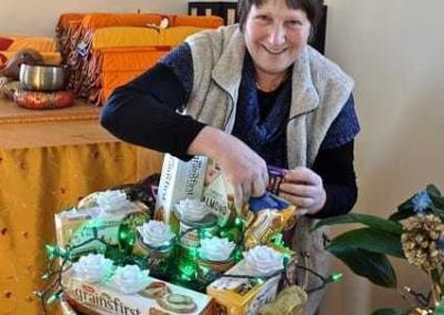smiling woman arranges food basket