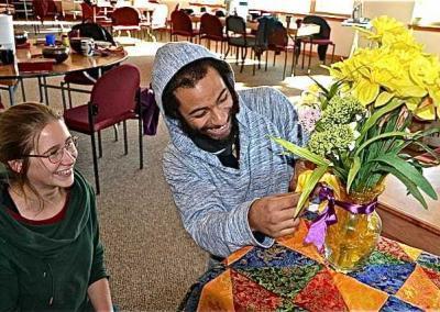 smiling man arranges flowers