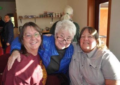 three smiling women pose for camera