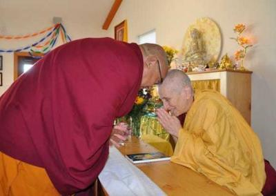 standing monk touches head to seated nun