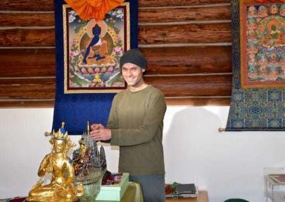 man dusts Buddhist statues