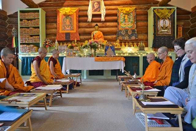 Two facing rows of nuns and laypeople sitting in meditation hall