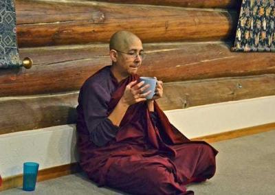 Nun sitting on floor holding cup