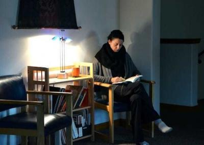 Woman reading in dark room by lamp