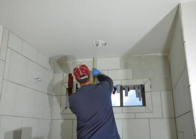 With exacting precision, Eric installs the ceramic bathroom tile.