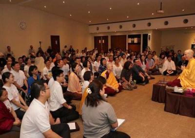 audience sitting on the floor listening to nun