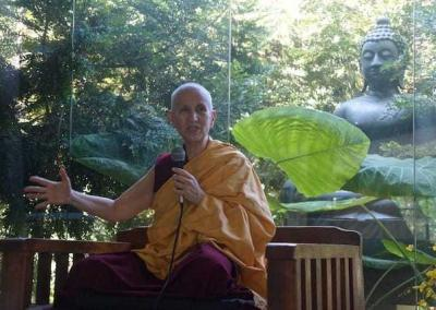 nun sitting in front of a large window with large Buddha statue